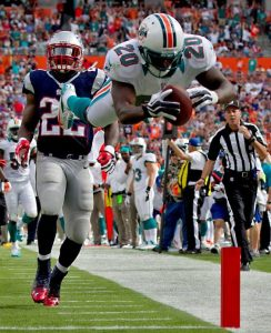 Reshad Jones dives into the end zone against New England Patriots.