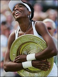 Venus Williams smiles with her Wimbledon trophy.